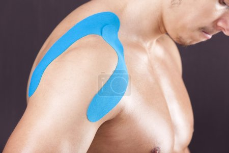 Muscular man with kinesiotaping on the shoulder