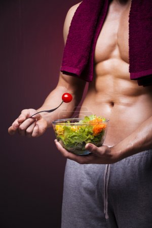 Muscular man holding a bowl of salad