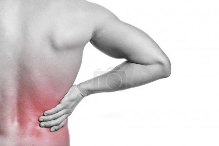 Muscular man holding his back in pain