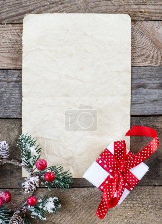 Foto de Hoja de papel con regalo de Navidad y holly sobre fondo de madera - Imagen libre de derechos
