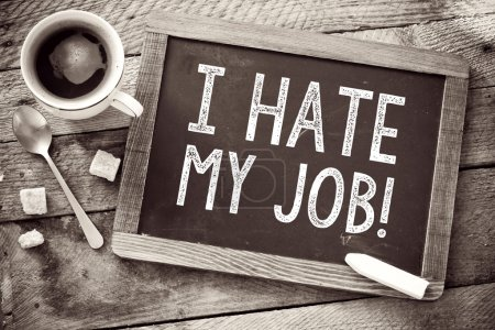 Blackboard with I Hate My Job sign and cup of coffee on wooden background