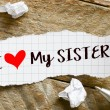 Note with I love my sister and red heart on the wo...