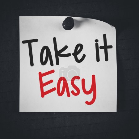 Photo pour White stick note paper with take it easy on blackboard background - image libre de droit