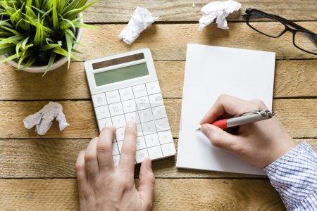Foto de Manos con calculadora y Bloc de notas, pluma, planta verde sobre fondo de madera - Imagen libre de derechos