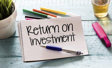 Photo pour Bloc-notes avec retour sur investissement et marqueurs, stylo, plante verte et boisson sur fond en bois - image libre de droit