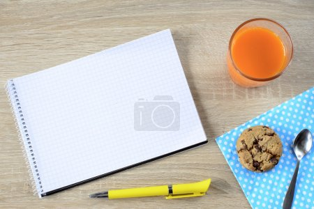 Carrot juice with cookie and empty notepad