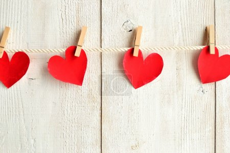Red heart paper cut out with clothes pins