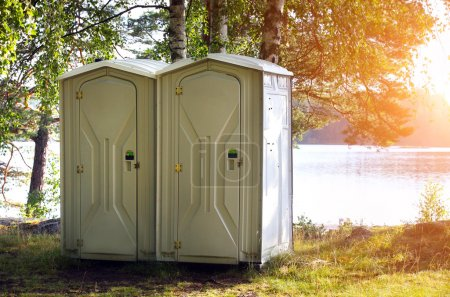 Photo for Two portable toilet or loo in blue plastic at a park - Royalty Free Image