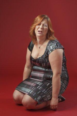 Foto de Mujer de pelo rojo, de rodillas, un berrinche - Imagen libre de derechos