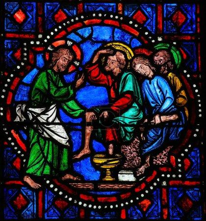 Foto de Vidriera que representa a Jesús lavando los pies de San Pedro en la última cena el jueves en la Catedral de tours, Francia. - Imagen libre de derechos