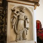 Постер, плакат: Statue of a saint holding a cross with a serpent draped about it