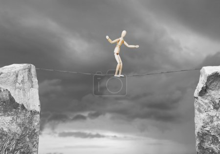 Man goes along a rope over the precipice