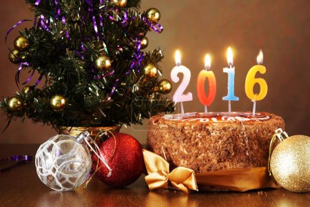 New Year 2016 still life. Chocolate cake and artificial fir tree with burning candles on brown background