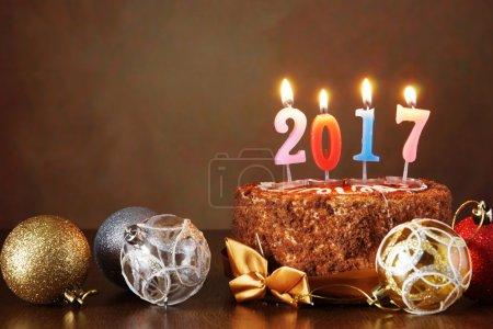 Photo pour Nouvel An 2017 nature morte. Gâteau au chocolat et boules d'arbre décoratives avec des bougies allumées sur fond brun - image libre de droit
