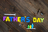 Letters and tools wooden background fathers day