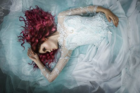 Photo for Woman lying on a dress and a tulle - Royalty Free Image