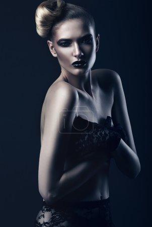Photo pour Belle femme avec des lèvres noires sur fond sombre - image libre de droit