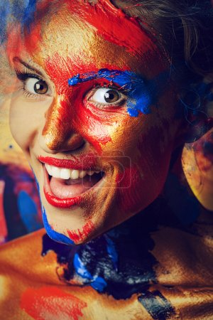 Cheerful girl in paints