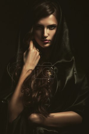 Photo for Mysterious woman in black cape  on dark background - Royalty Free Image