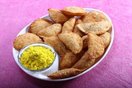 Photo pour Gujia, snacks traditionnels indiens pour le festival holi avec couleur jaune dans le bol - image libre de droit