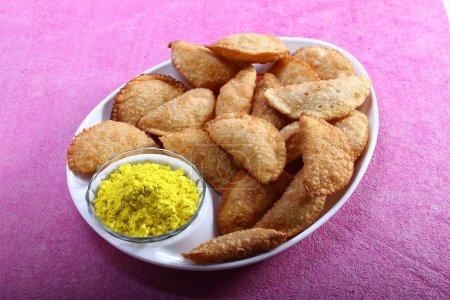 Photo pour Collation traditionnelle indienne Gujiya servi dans une assiette avec Holi couleur dans un bol - image libre de droit