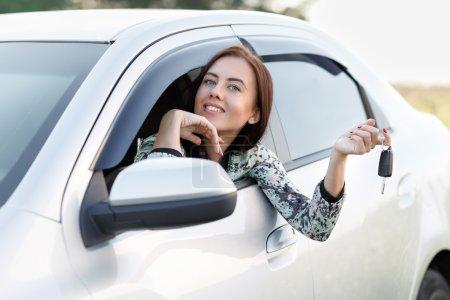 Photo pour Souriant belle fille dans la voiture tient les clés - image libre de droit