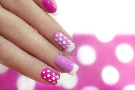 Photo pour Nail design avec des points blancs sur le Français manucure avec vernis rose de divers tons. - image libre de droit