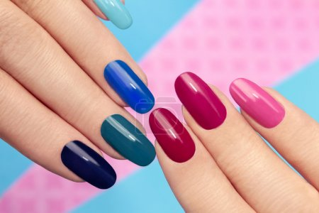 Photo for Blue pink nail Polish on long nails on a colored background. - Royalty Free Image