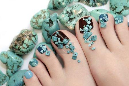 Photo pour Pédicure avec des pierres turquoise et des bijoux en turquoise sur le pied des femmes - image libre de droit