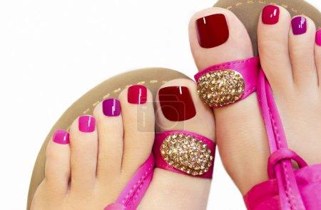 Photo pour Pédicure avec différentes couleurs de peinture sur les pieds d'une femme en sandales roses sur fond blanc . - image libre de droit