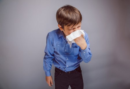 Teenager boy of 10 years of European appearance sick sneezing in a handkerchief, runny nose, temperature