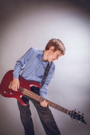 teenager boy of 10 years European appearance playing guitar o