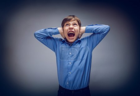 teenager boy shouts shut his ears opened  mouth on