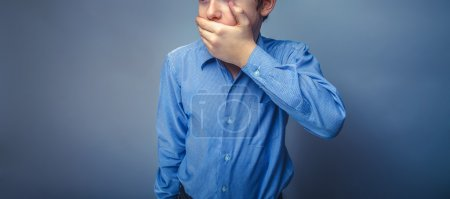 Photo pour Teen boy European appearance brown hair hand closed mouth feels fear unknown - image libre de droit