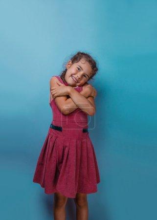 Girl European appearance decade hugging herself on a blue backgr