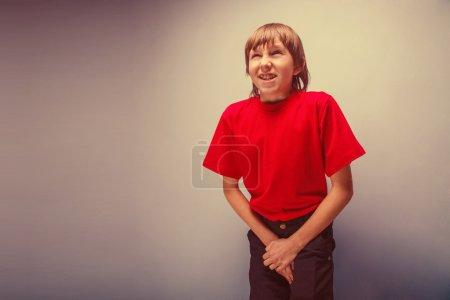 Photo pour Garçon, adolescent, douze ans dans la chemise rouge veut utiliser les toilettes, cystite rétro - image libre de droit