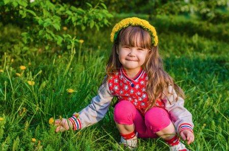 Beautiful little girl picking flowers