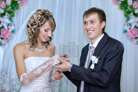 Groom putting a wedding ring on bride finger