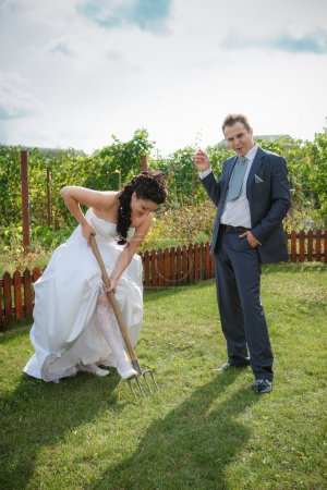 Bride and groom digs the soil on a kitchen garden.