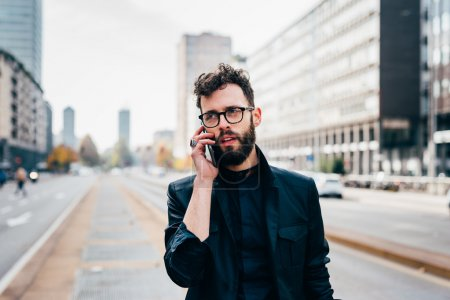 businessman in city talking on smartphone