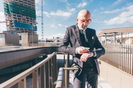 businessman in city using smartphone