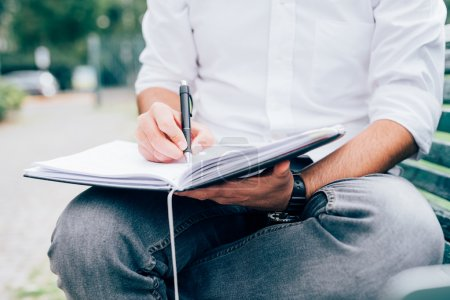 man writing on his agenda