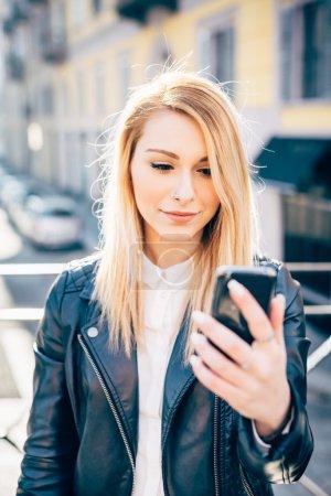 Photo pour Demi-longueur de la femme jeune belle chevelure blonde millénaire dans la ville lumière arrière emportant selfie téléphone intelligent main tenir - image libre de droit