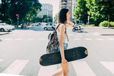 woman walking holding a skateboard