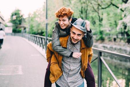 Photo pour Jeune couple de caucasiens beaux amants homme et femme en plein air dans la ville contre-jour, en s'amusant étreignant amour, relation, concept de bonheur - image libre de droit