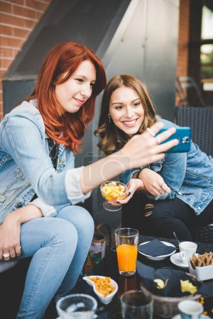 Photo for Two young handsome blonde and redhead straight hair women sitting in a bar taking a selfie with smartphone - technology, social network, vanity concept - Royalty Free Image