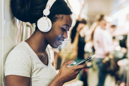 Photo pour Demi-longueur de belle jeune afro noire femme voyageant dans métro, écoute de musique avec des écouteurs et tapant écran de main téléphone intelligent hold - technologie, relaxant, le concept de réseau social - image libre de droit