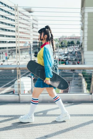 asian woman walking holding skateboard
