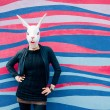 Three quarter length woman wearing rabbit mask outdoor in the city leaning against colorful wall - halloween, dreamlike, strange concept