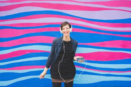 woman leaning against wall listening music